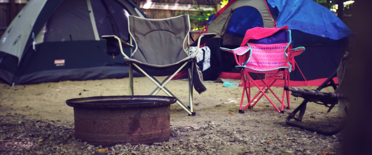 Tents and chairs around a fire pit