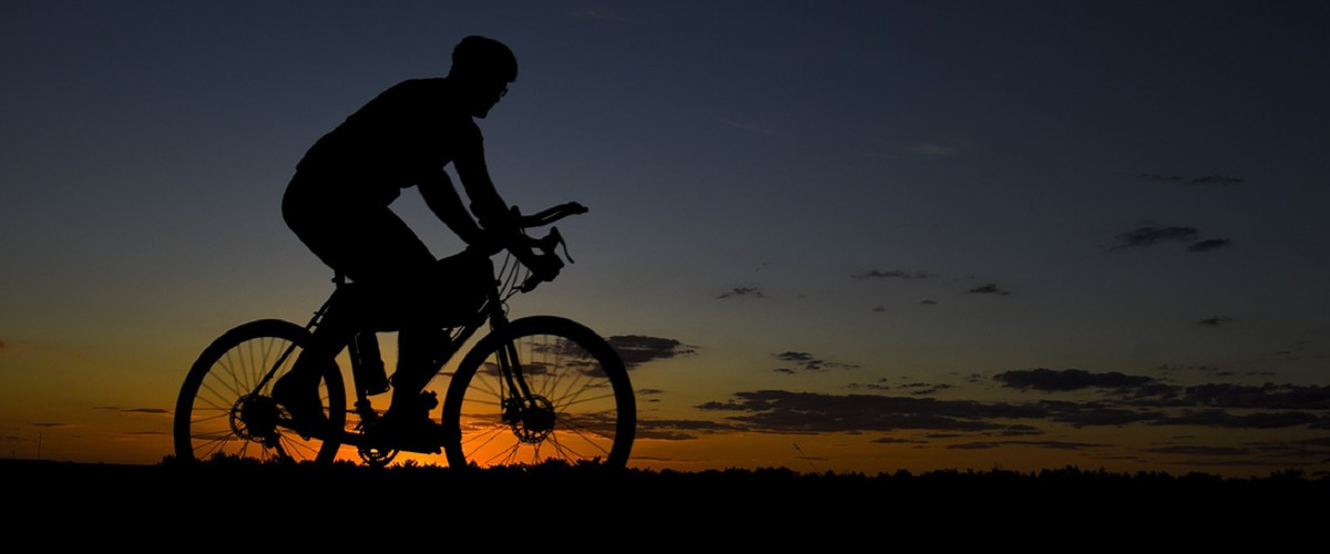 Person biking at sunset