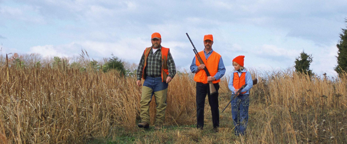 Men and a child hunting in a field